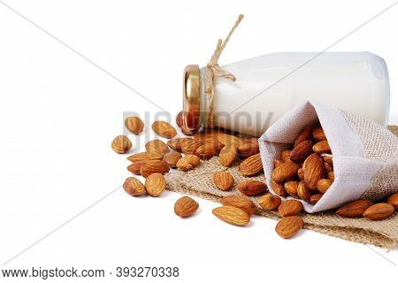 Glass Bottle Of Milk With Almond In Hemp Fabric Bag Isolated On White Background. Homemade Almond Mi