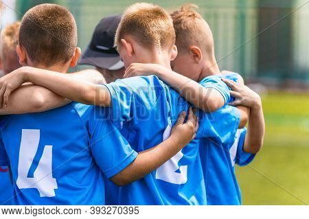 Kids Soccer Team With Coach In Group Huddle Before The Match. Elementary Age Children Are Listening