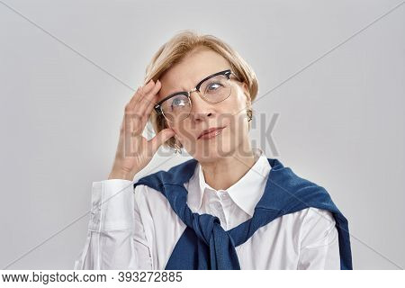 Portrait Of Elegant Middle Aged Caucasian Woman Wearing Business Attire And Glasses Having A Thought