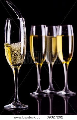 Full glasses of champagne and one being filled against black background poster