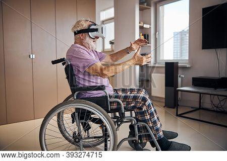 Senior Caucasian Gamer Immersing Himself In Virtual Reality
