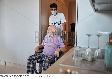 Young Dark-haired Volunteer Taking Care Of The Disabled Person