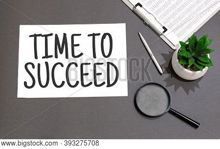 Top View Of Magnifying Glass,calculator,pen, Plant And Notebook Written With Time To Succeed Sign