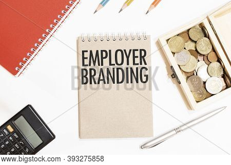 Calculator,red Notepad, Three Colour Pencils, Silver Pen And Brown Notebook With Text Employer Brand