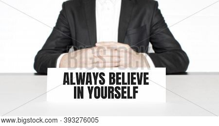 Businessman Sitting At The Table And Signboard With Text Always Believe In Yourself . Business Conce