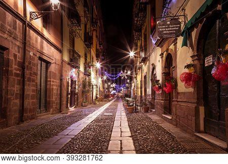 Bosa, Sardinia Island Italy - December 29, 2019: Tourist Relaxing During The Evening In The Ancient