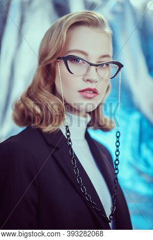 Beautiful young woman in formal clothes and elegant fashionable spectacles. Business style. Beauty, fashion. Optics and eyewear style.