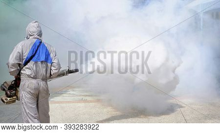Rear View Of Health Personal Worker Using Fogging Machine Spraying Chemical To Eliminate Mosquitoes
