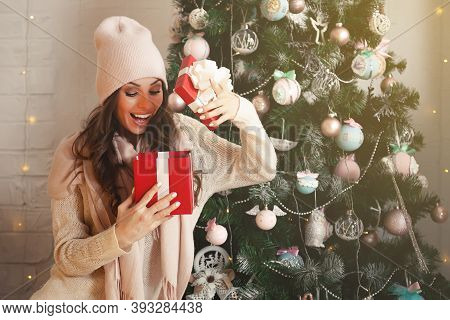 Smiling And Happy, Beautiful Young Woman In Winter Clothes With A Red Christmas Gift Box On The Back