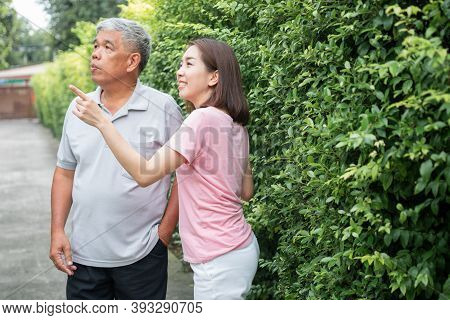 An Old Elderly Asian Man And Walking In The Backyard With Her Daughter.  Concept Of Happy Retirement
