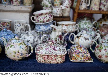Porcelain Objects With A Floral Theme In A Stand On A Flea Market