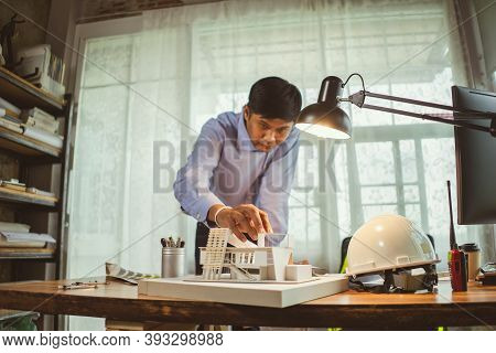 Asian Man Architect Making Architecture Model Of House. Man Architect Working In The Office. Archite