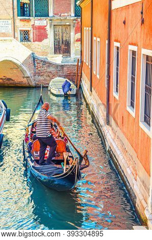 Venice, Italy, September 13, 2019: Bold Gondolier On Gondola With Tourists People Sailing In Narrow