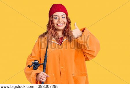 Young latin woman wearing fisher raicoat holding rod smiling happy and positive, thumb up doing excellent and approval sign