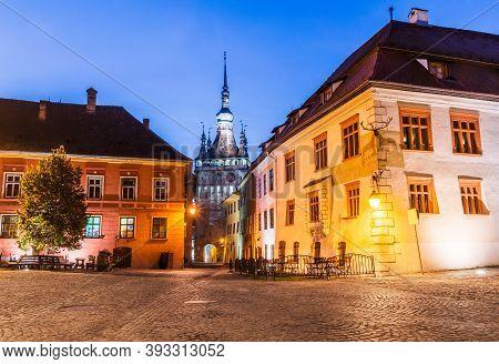 Sighisoara, Romania. Medieval Street At Twilight With Clock Tower In Transylvania.
