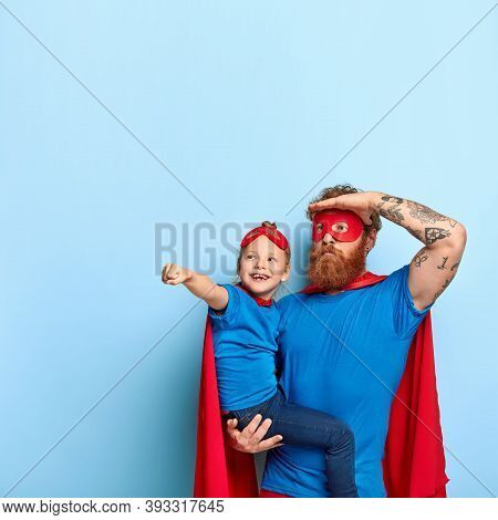 Photo Of Father And Daughter Play Together, Wear Superhero Costumes, Happy Small Child On Dads Hands