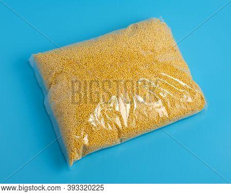 millet groats pack on blue background