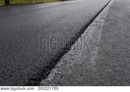 A Large Layer Of Fresh Hot Asphalt. Layer Of Asphalt Raw Material In A Shallow Depth Of Field. Rolle