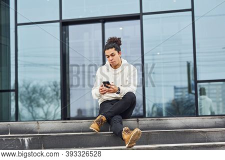 Handsome Young Man With Curly Black Hair And With Smartphone In Hands Is On The Street Sitting On Th