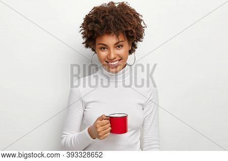 Portrait Of Happy Curly Haired Woman With Toothy Smile, Holds Red Mug Of Hot Drink, Looks Straightly