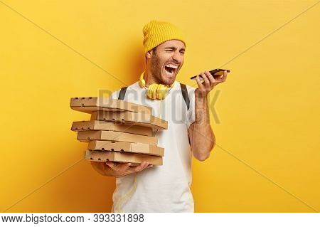 Photo Of Annoyed Pizza Man Courier Screams Angrily At Smartphone, Has Annoying Conversation With Cli