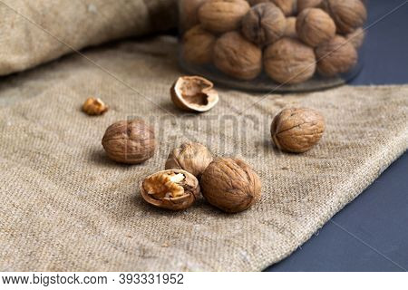 Close-up Three Walnuts. Unpeeled And Peeled Walnuts In Shells On A Black Table And In A Glass Jar. B