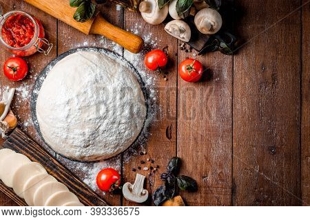 Ingredients For Making Pizza - Dough, Mozzarella Cheese, Tomatoes, Mushrooms And Basil On A Wooden B