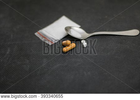 Frontal View In The Foreground, Of Some Pills And Capsules, Placed In Front Of A Teaspoon With Cocai