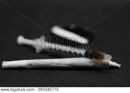Close-up Photo Of A Syringe Full Of Cocaine, Placed On A Barrel Of Marjiuana And Cocaine, Both Place