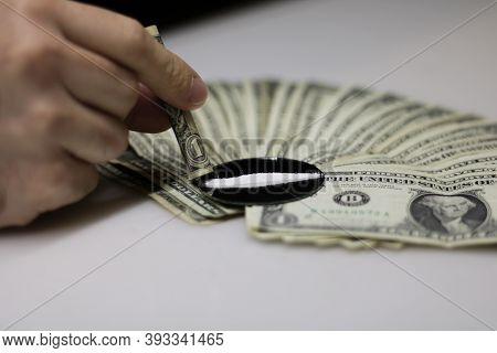 Frontal And Close-up View Of A Fan Of Dollar Bills Deriving From The Cocaine Trade, While A Strip Of