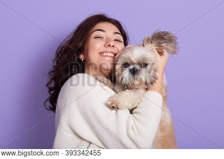 Playful Smiling Female Embraces Small Pekingese Dog, Have Fun Together, Friendly Relationship, Dark