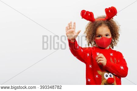 A Little African American Girl In A Face Mask On And A Horns Of Small Deer Makes Gesture With Open P