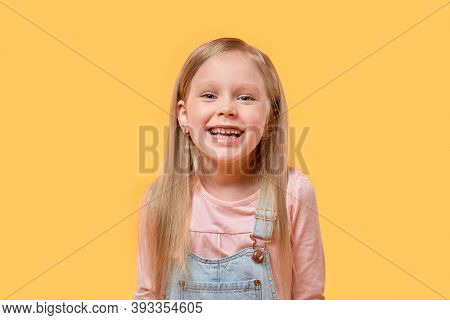 Portrait Of A Blonde Girl Smiling And Looking At The Camera. Yellow Background.