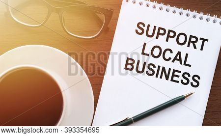 Support Local Business Text Written On A Notepad On A Table With A Cup Of Coffee, Glasses And A Pen,