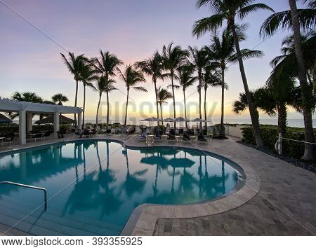 Naples, Fl/usa - 10/30/20: Sunset Overlooking The Gulf Of Mexico With Lounge Chairs And Palm Trees A