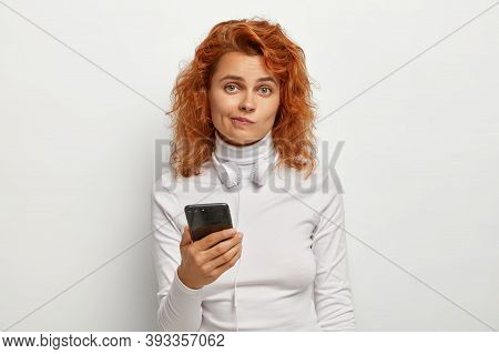 Attractive Confused Redhead Woman Meloman Listens Music Via Headphones Connected To Smartphone, Down