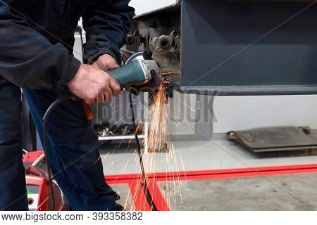 A Welder Welds And Assembles A Truck Trailer Part In A Garage. Service Of Trailers And Cars.