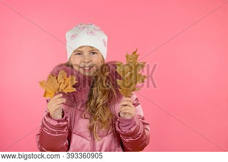 Little Girl In A Winter Pink Coat On A Pink Background. Little Fashionista Trying On A Pink Coat. Gi
