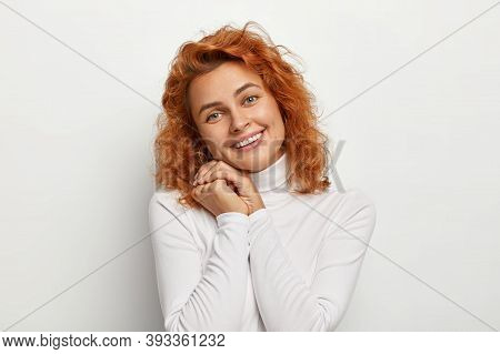 Portrait Of Charming Redhead Young Woman Keeps Hands Together, Tilts Head And Smiles Gently, Receive