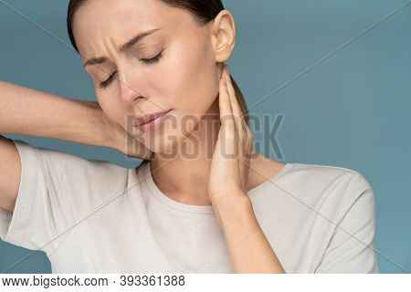 Woman Suffering From Chronic Neck Pain, Gently Massages With Hands, Feeling Tired After Long Hours W