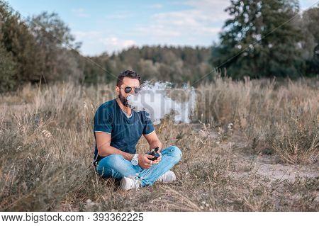 Modern Vaper Using Electronic Cigarette To Vape Instead Of Smoking. Electronic Cigarette As Alternat