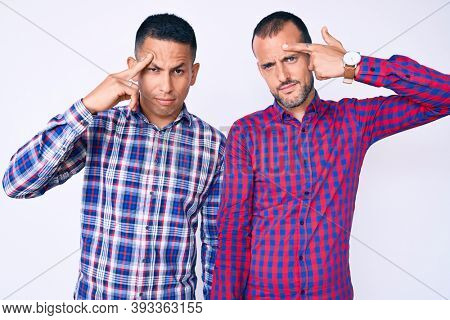Young gay couple of two men wearing casual clothes pointing unhappy to pimple on forehead, ugly infection of blackhead. acne and skin problem