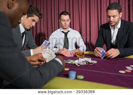 Men playing high stakes poker game in casino
