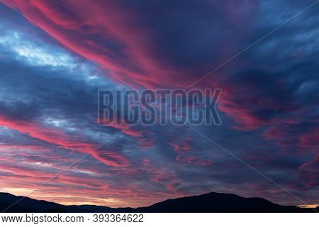 Fiery purple sunset sky. Dramatic sky with pink glowing clouds. Natural background for your landscape project