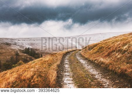Amazing scene on autumn mountains. Orange grass, first snow and rural road in fantastic morning sunlight. Landscape photography