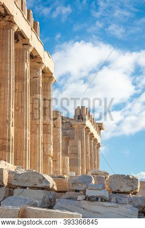 Doric Columns Of The Parthenon Against A Blue Sky With Clouds, Acropolis In Athens