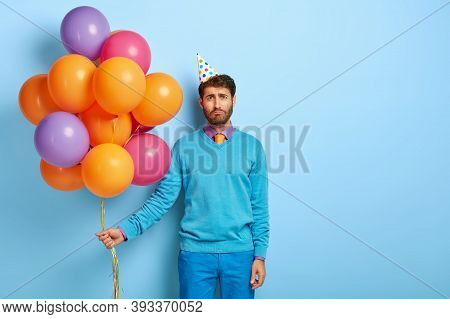 Studio Shot Of Gloomy Upset Man Looks Unhappily At Camera, Feels Lonely During His Birthday, Holds B