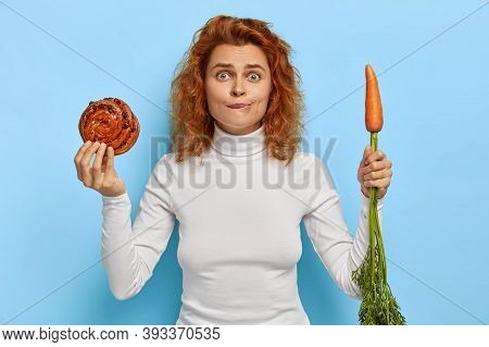 People, Nutrition, Dieting And Junk Food Concept. Embarrassed Redhead Woman Holds Fresh Tasty Bun An