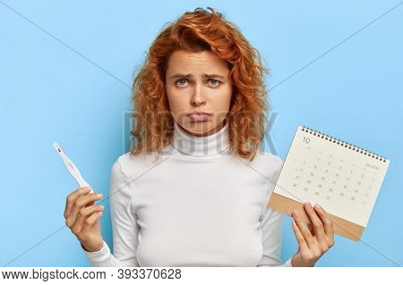 Sad Disappointed Redhead Woman Holds Pregnancy Test And Menstruation Calendar, Gets Unexpected Resul