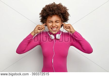 Discontent Afro Woman With Curly Hair, Plugs Fingers In Ear Holes, Ignores Unpleasant Loud Noise, He